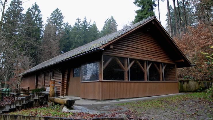 Die Waldhütte mit dem davor stehenden Brunnen.