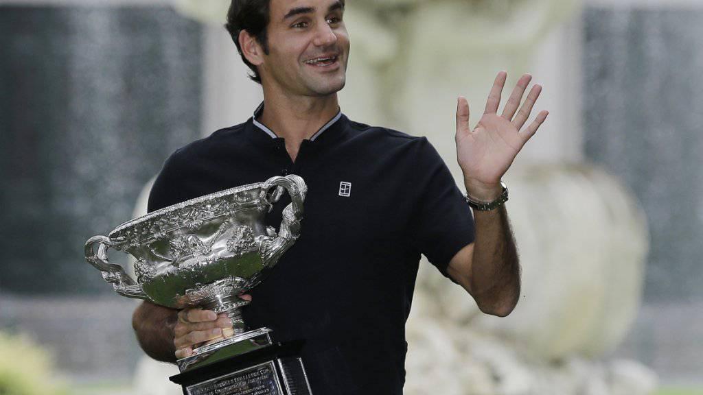Strahlender Sieger: Roger Federer präsentiert den Pokal am Tag nach seinem Triumph in den Melbourner Carlton Gardens
