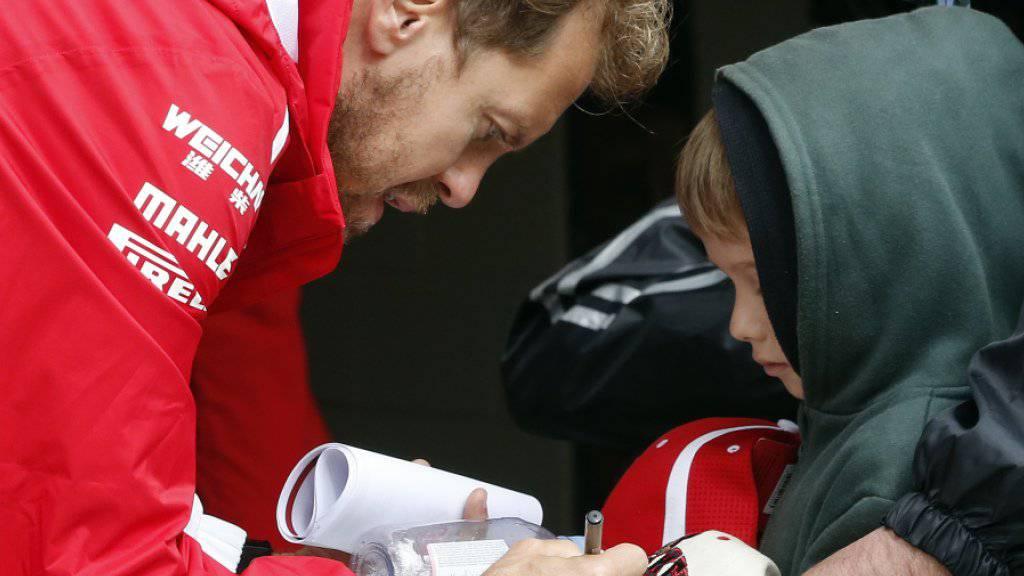 Sebastian Vettel nimmt sich Zeit, um noch Autogramme für die Kleinsten zu schreiben