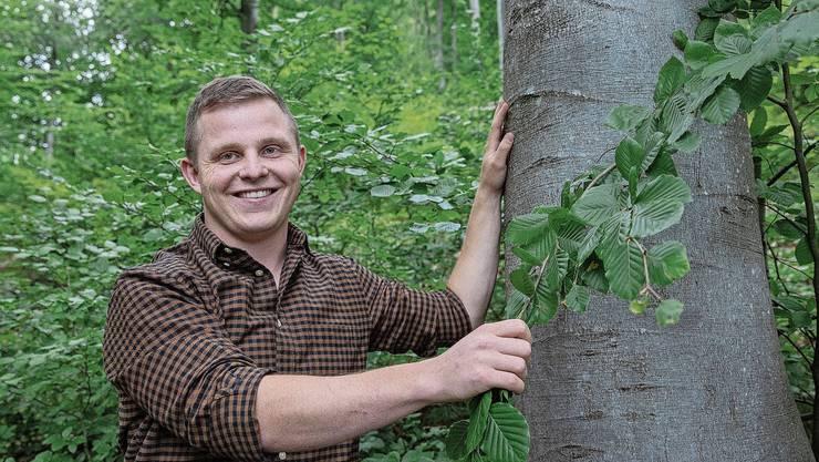 Joshua Huber im Balsthaler Wald neben einer Buche, die ungefähr viermal älter ist als der neu erkorene Kreisförster.