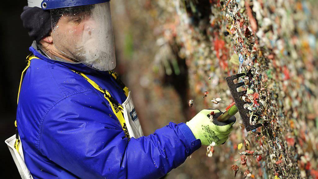 Eine Reinigungskraft entfernt Kaugummis von einer Wand in Seattle.
