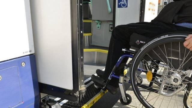 Ein Mann im Rollstuhl rollt in ein Genfer Tram (Archiv)
