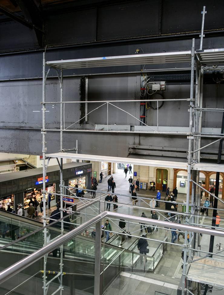 Im Bahnhof SBB Basel folgt eine Anzeigetafel auf eine Werbetafel oberhalb der Rolltreppe zur Schalterhalle