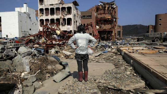 Eine Frau blickt nach dem Tsunami vom 11. März 2011 auf Onagawa