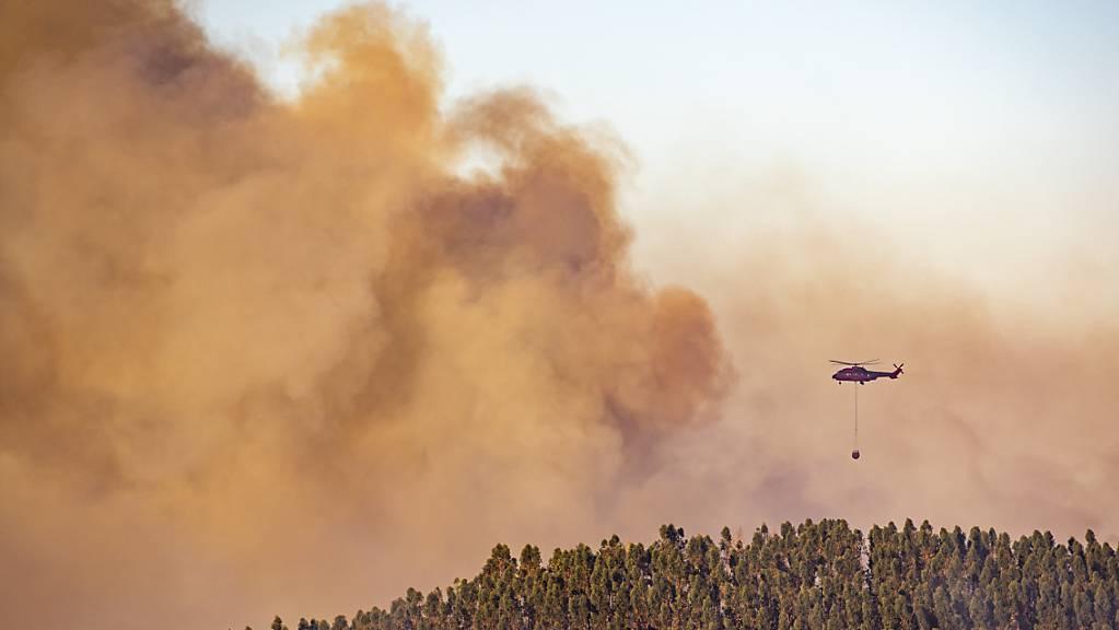 Ein Hubschrauber über den Rauchschwaden eines  Waldbrandes in der Gemeinde Almonaster la Real. Foto: A. Perez/Europa Press/AP/dpa