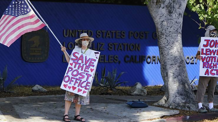 ARCHIV - Erica Koesler (l.) und David Haerle aus Los Angeles demonstrieren vor einem Postamt von USPS im Stadtteil Los Feliz. Foto: Chris Pizzello/AP/dpa