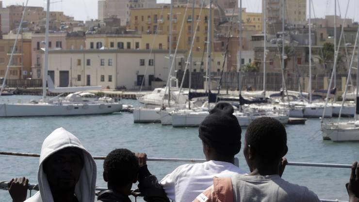 Auf dem Meer gerettete Flüchtlinge werden von einem Schiff an den Hafen der sizilianischen Stadt Trapani gebracht (Archiv).