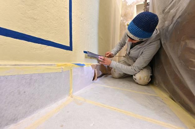 Eine Malerin streicht die Farbe entlang des Lineals auf die Wandoberfläche.