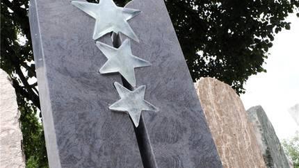 Die Sterne des Anstosses: Grabstein mit drei Glassternen.