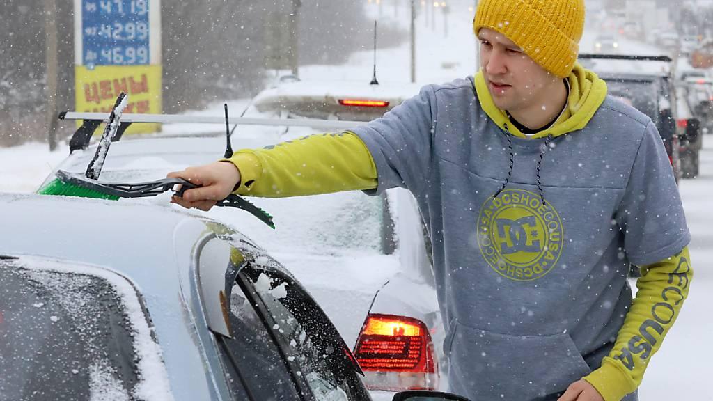 Ein Mann wischt bei Schneefall Schnee von einem Auto auf der Dmitrovskoye-Autobahn. Nach stundenlangen starken Schneefällen und -stürmen steuert die russische Hauptstadt Moskau auf eine Rekordschneedecke zu. Foto: Vladimir Gerdo/TASS/dpa