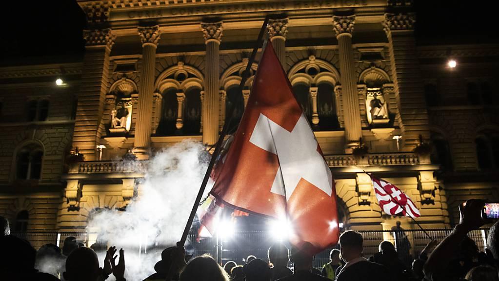Demonstranten schwenken Fahnen hinter einem Zaun vor dem Bundeshaus auf dem Bundesplatz.