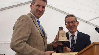 Regierungsrat Urs Hofmann überreicht Gemeindeammann Daniel Suter eine Glocke als Geschenk zum Einzug. hcw
