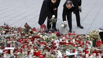 Die deutsche Kanzlerin Merkel und der französische Präsident Hollande legen zum Gedenken an die Opfer des Anschlags auf einen Berliner Weihnachtsmarkt Blumen nieder.