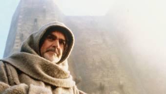 """Sean Connery in """"Der Name der Rose"""" vor dem Kloster Sacra di San Michele bei Sant'Ambrogio di Torino. Das Gebäude wurde in der Nacht von Mittwoch auf Donnerstag durch ein Feuer schwer beschädigt. (Pressebild)"""