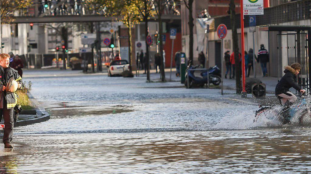 Ein Kind fährt durch die von Sturmtief «Herwart» überflutete Hafencity in Hamburg. (Bild vom Sonntag)