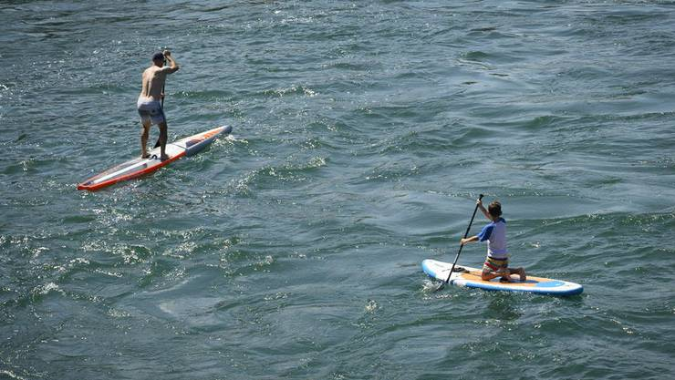 Sie geniessen die Sonne auf dem Stand Up Paddle: Zwei Männer in Diessenhofen.