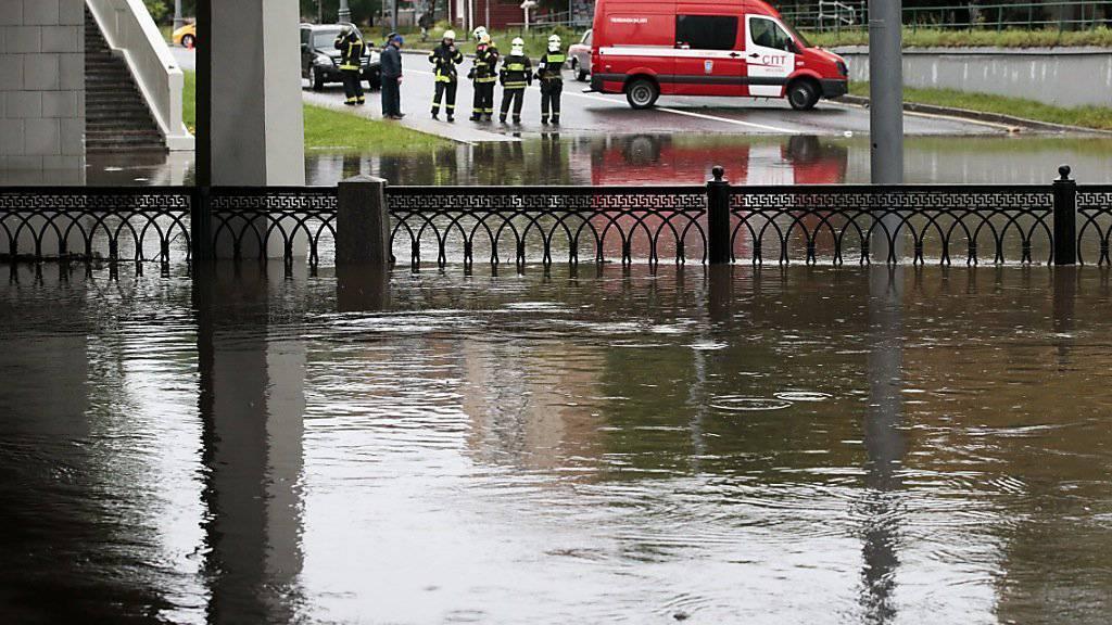 Retter unterstützen die Bewohner Moskaus an überschwemmten Strassen.