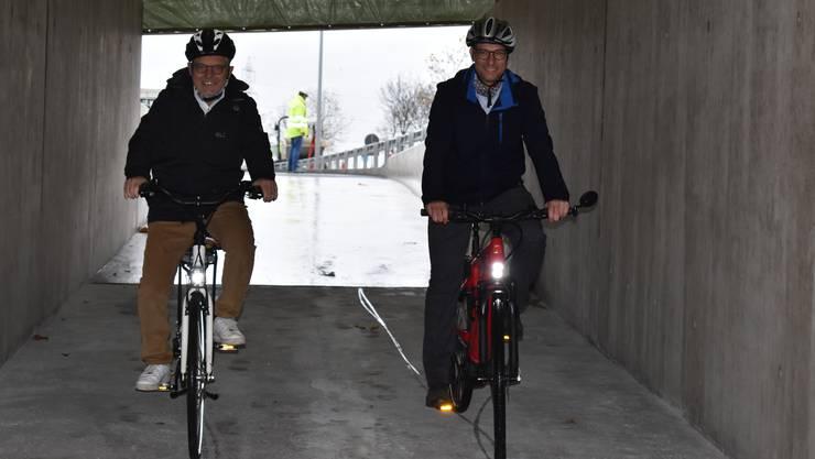Gemeinderat Jean Frey (links) und Martin Bühler vom kantonalen Baudepartement auf der Probefahrt durch die neue Velounterführung.