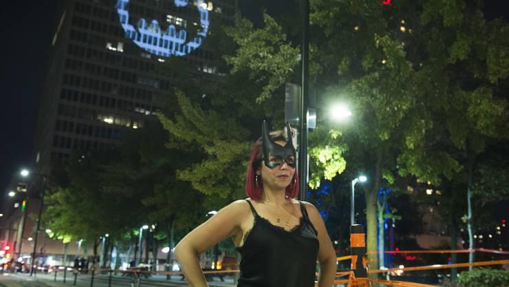 Ein Batman-Fan posiert vor einem Leuchtsignal in der kanadischen Metropole Montreal.