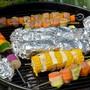 Jetzt sehen sie lecker aus – aber davor waren sie bunter: Hackbällchen abwechselnd in Zucchetti und Karottenstreifen eingepackt. In den Alufolie-Päckchen daneben garen das übrig gebliebene Rüst-Gemüse und Grillkäse.