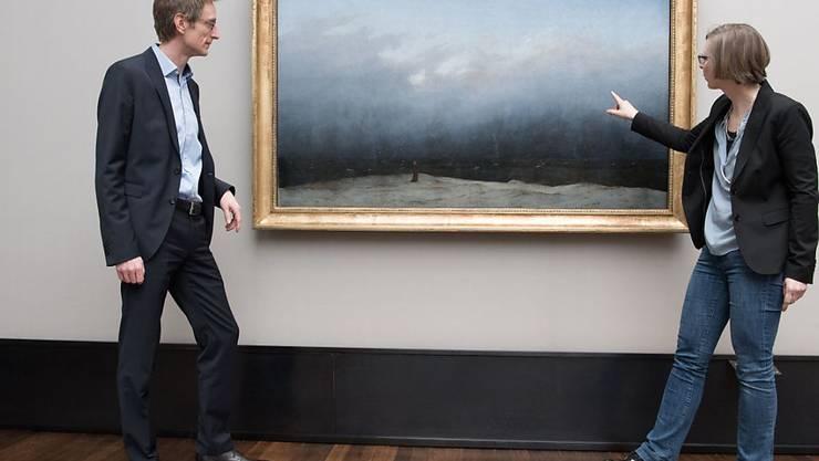 """Ralph Gleis, Leiter der Alten Nationalgalerie in Berlin, und Yvette Deseyve, Kuratorin der Ausstellung """"Mit dem Mönch am Meer - Caspar David Friedrich in Virtual Reality"""" vor dem Original: Bis zum 30. Juni können Besucher das Werk virtuell mit Hilfe einer 3D-Brille erleben."""