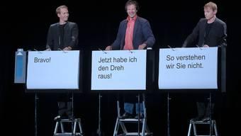 Das Kabarettduo «Ohne Rolf», Jonas Anderhub (l.) und Christof Wolfisberg (r.), mit einem Zuschauer in der Rolle des Bewerbers Heinrich Banzer (Mitte).