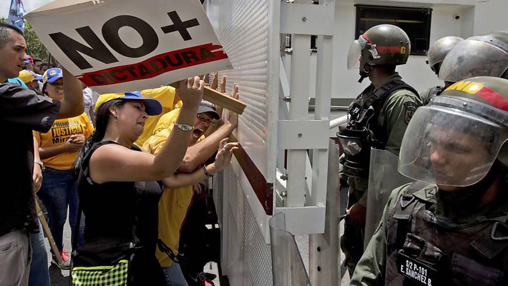 """""""Keine Diktatur mehr"""" steht auf dem Plakat, das diese Demonstrantin in Venezuelas Hauptstadt Caracas zur Schau trägt. Laut der Opposition geht der Staatsstreich im Land weiter."""