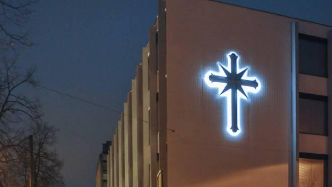 Das Kreuz an der Wand der Ideal Org leuchtet in der Nacht. Foto: Martin Töngi