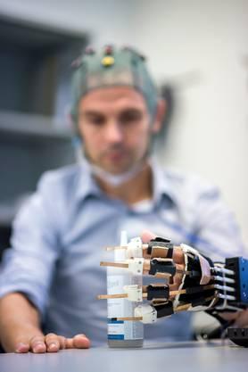 Mittels einer an der ETH Lausanne entwickelten Schnittstelle kann ein Schlaganfallpatient via Elektroden am Kopf die Nerven des gelähmten Arms ansteuern. Bild: Keystone