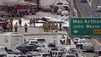 Die Cessna liegt in einer Lache aus Löschschaum, der Highway ist komplett gesperrt: Wie durch ein Wunder überlebten die beiden Insassen die Bruchlandung des Kleinflugzeugs.