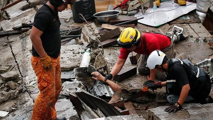 Rettunskräfte bergen einen Mann, der bei einem Mauereinsturz während eines Unwetters in Manila verschüttet wurde.