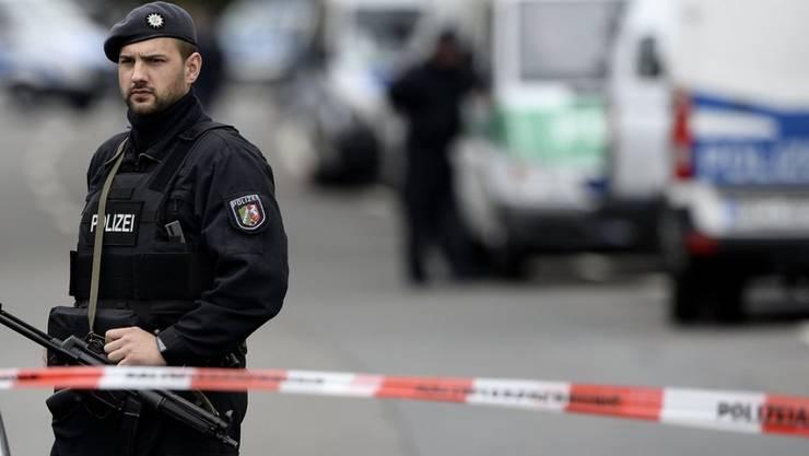 Ein Polizist steht in Dortmund hinter einer Absperrung. Im Zusammenhang mit dem Anschlag auf den BVB-Mannschaftsbus wurde ein Verdächtiger festgenommen. Die Bundesanwaltschaft spricht von einem terroristischen Hintergrund.