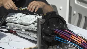 Ein Techniker fädelt ein Glasfaserkabel ein (Symbolbild)