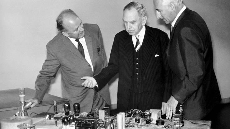 Otto Hahn (Mitte) und Fritz Strassmann (links) erklären an ihrem ehemaligen Arbeitstisch das Kernspaltungsexperiment.
