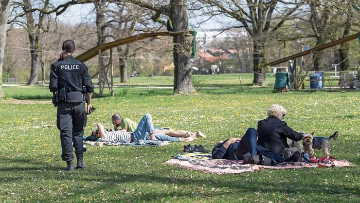 Auch Liebespaare müssen eigentlich Abstand halten: Eine Polizistin in einem Park bei Genf.