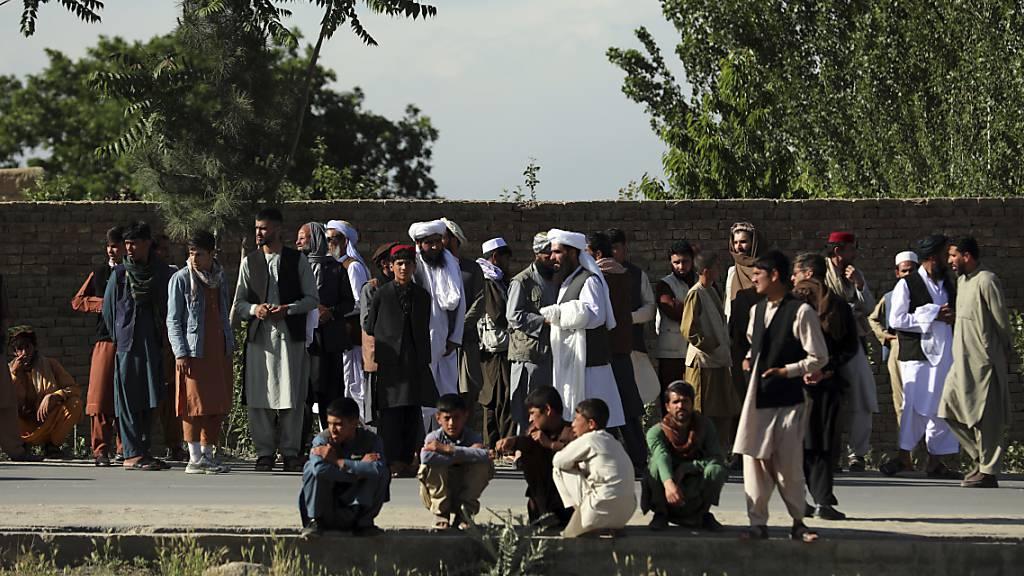 Menschen versammeln sich in der Nähe einer Moschee nach einer Bombenexplosion in Kabul. Bei dem Anschlag sind nach Angaben der Polizei mindestens zwölf Menschen getötet worden. Foto: Rahmat Gul/AP/dpa