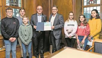 Hans Künzle (4.v.l.), Präsident UNICEF Schweiz und Liechtenstein, übergibt im Beisein einiger Badener Schülerinnen und Schüler das Zertifikat an Stadtammann Markus Schneider. Bild: Sandra Ardizzone