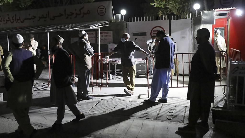 Afghanen warten vor dem Krankenhaus auf ihre Angehörigen. In Afghanistan detoniert eine massive Autobombe bei einem Gästehaus in der zentralen Provinz Logar. Unter den zahlreichen Opfern sind vor allem Schüler. Foto: Rahmat Gul/AP/dpa