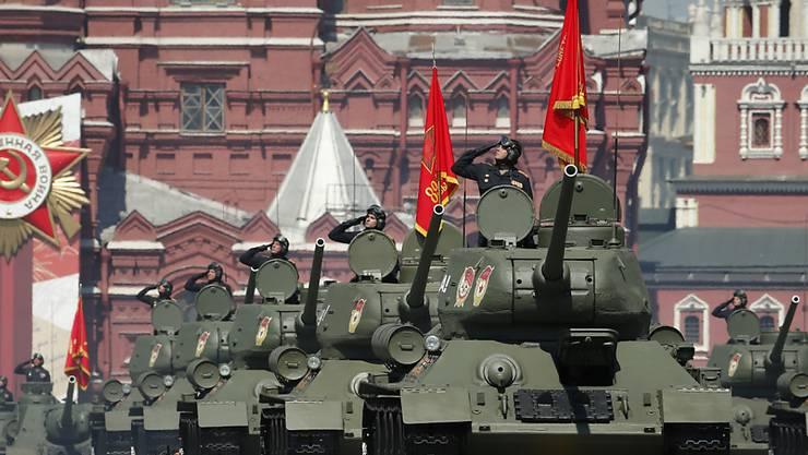 Sowjetische T-34-Panzer fahren bei der Militärparade zum 75. Jahrestag des Sieges der Sowjetunion über Hitler-Deutschland zum Roten Platz. Foto: Alexander Zemlianichenko/AP/dpa