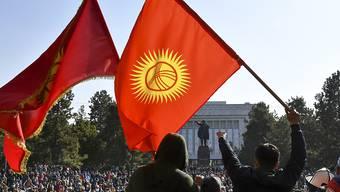 Die Demonstranten schwenken der kirgisischen Fahnen, während sie auf die Rede des kirgisischen Premierministers Schaparow vor dem Regierungsgebäude warten. In Kirgistan ist nach massiven Protesten der Oppositionelle Schaparow vom Parlament als neuer Regierungschef bestätigt worden. Foto: Vladimir Voronin/AP/dpa