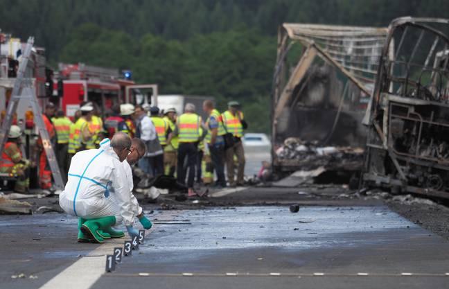 Experten der Polizei arbeiten an der Unfallstelle auf der Autobahn A9 vor dem ausgebrannten Anhaenger eines Lkw.