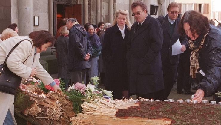 Trauernde zünden am Samstag, 29. November 1997, am Mahnmal der Künstler Remigius Graf und Markus Fritschi vor dem Grossmünster in Zürich, wo die nationale Trauerfeier für die Opfer von Luxor stattfand, Kerzen an.