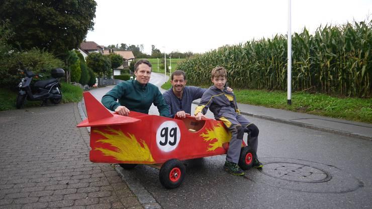 Posieren stolz vor der roten Seifenkiste: Mathias Wenger (OK), Alex Gisler (OK-Präsident) und Tys Gisler (von links).