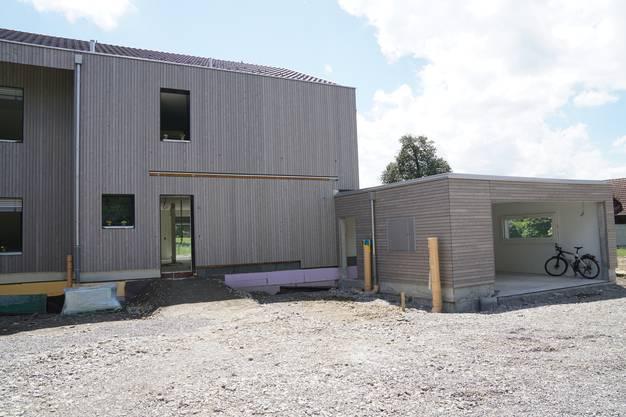 Im Wohnbereich verläuft die Holzverschalung senkrecht, bei den Nebenbauten waagrecht.