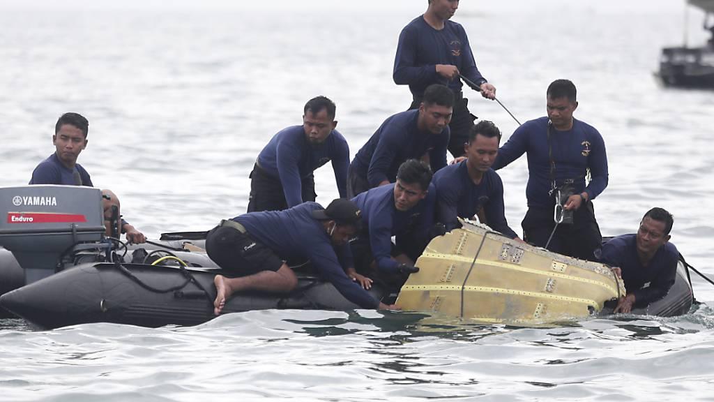 Taucher der indonesischen Marine ziehen ein Flugzeugteil aus dem Wasser. Foto: Achmad Ibrahim/AP/dpa