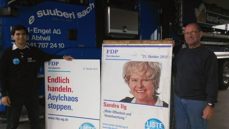Grossratskandidat Yatin L. Shah (links) und FDP-Vorstandsmitglied Peter Engel mit einem von Vandalen beschädigten, wieder instand gestellten Plakatständer