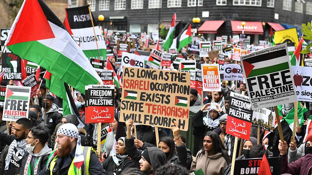 Demonstranten halten Plakate und palästinensische Flaggen während eines Protests in London. Tausende Menschen haben in der britischen Hauptstadt gegen die Luftangriffe der israelischen Armee auf Gaza demonstriert. Foto: Dominic Lipinski/PA Wire/dpa