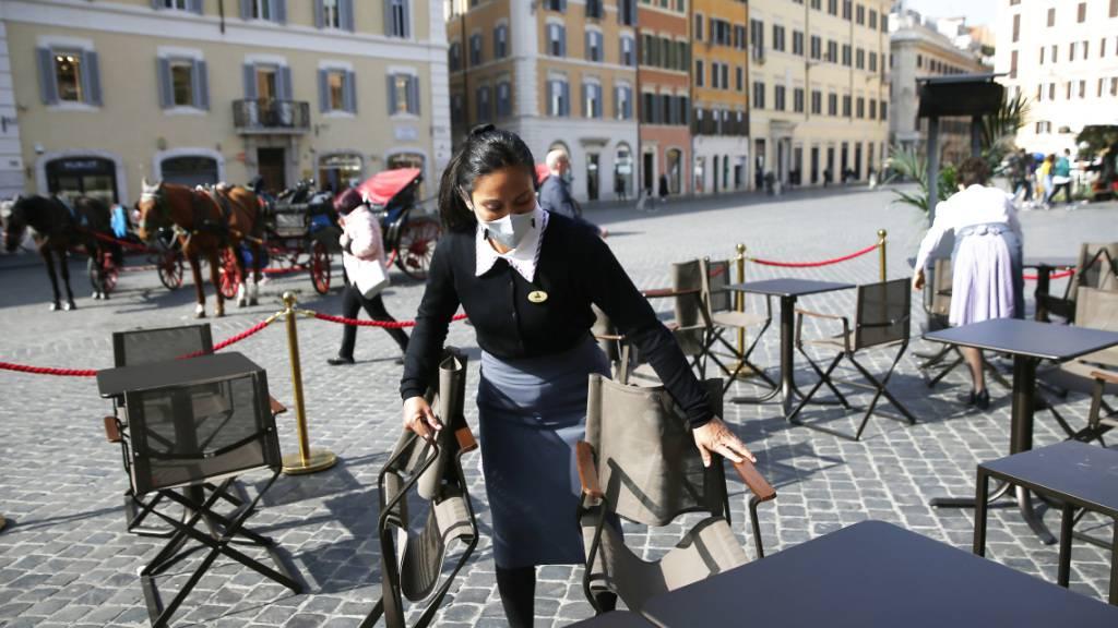 Wie geht es weiter? Eine Mitarbeiterin bereitet Tische im Außenbereich eines Cafes nahe der Spanischen Treppe in Rom vor. Die italienische Regierung plant eine neue Verordnung mit Anti-Covid-Vorlagen zu verabschieden, die vom 6. März bis zum 6. April gültig sein soll. Foto: Cecilia Fabiano/LaPresse via ZUMA Press/dpa