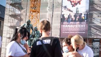 Ein neues Banner mit der Aufschrift «Kein Platz für Rassismus und Gewalt - Hanau steht zusammen für Respekt, Toleranz und Zivilcourage» hängt an der Fassade des Rathauses vor dem Gebrüder-Grimm-Denkmal. Foto: Frank Rumpenhorst/dpa