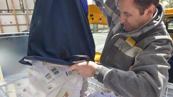 Ein Briefträger leert den Postsack voller Briefe (Symbolbild)